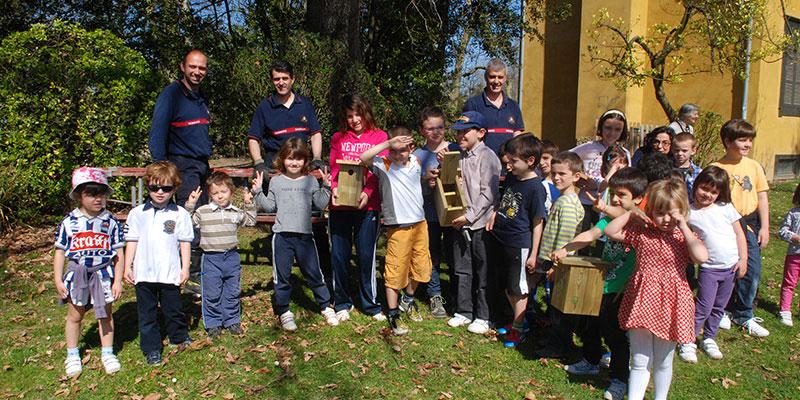 Grupo de niños y operarios tras la colocación de la caja-nido de pájaros
